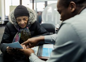 Edith Gyamfi getting tax advice from Tyrone Oliphant at a Jackson Hewitt branch in the Bronx on Tuesday. Credit Sasha Maslov for The New York Times